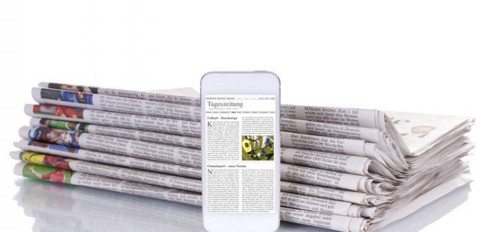 Stapel Zeitungen mit E-Paper Smartphone